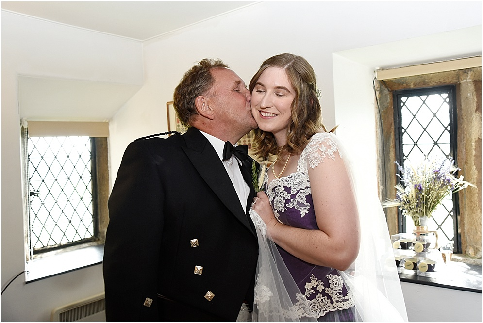 Bride gets a kiss from her dad in the cheek.