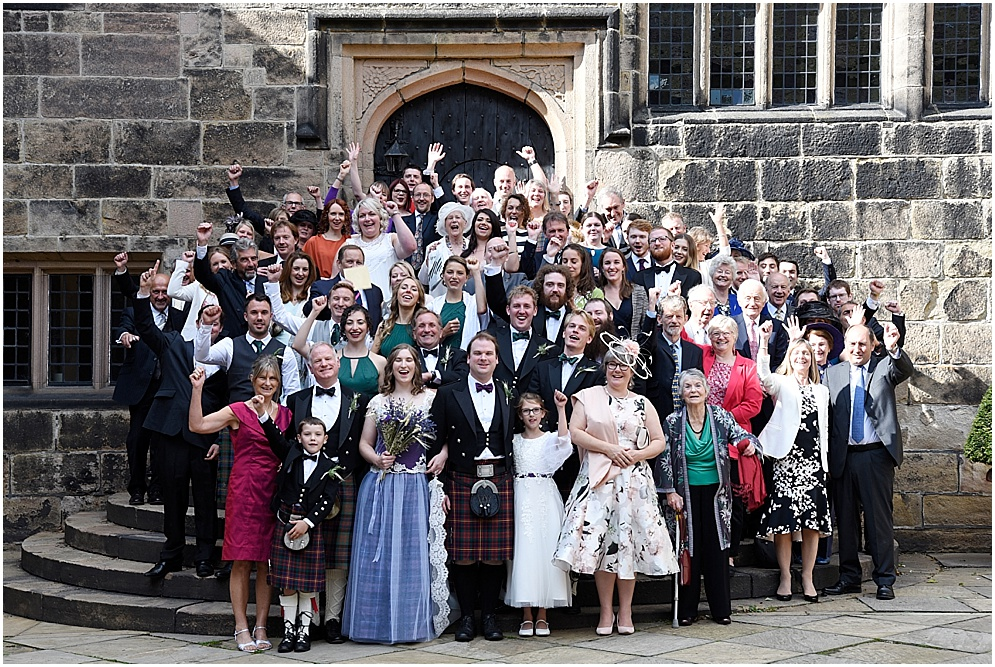 Smiling guests group photograph at a wedding at Hoghton Tower. Lancashire wedding photography.