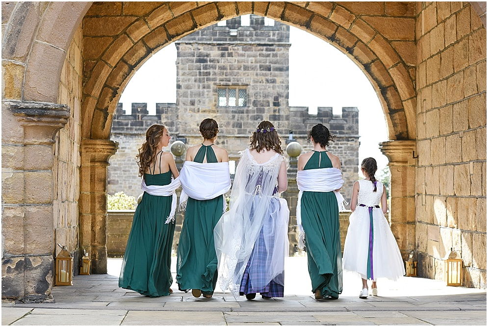 Bride and her bridesmaids walk under the archway at Hoghton Tower. Hoghton Tower wedding photography.