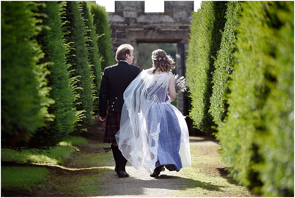 Summer wedding at Hoghton Tower. Bride and groom walk through the gardens.