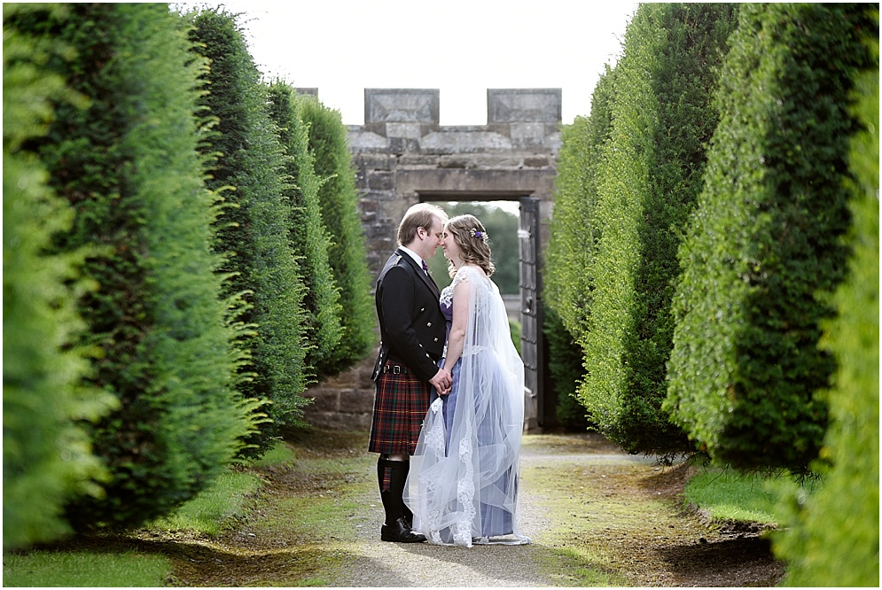Lancashire wedding photographer. Picture of a bride and groom pictured in the gardens at Hoghton Tower on their wedding day.