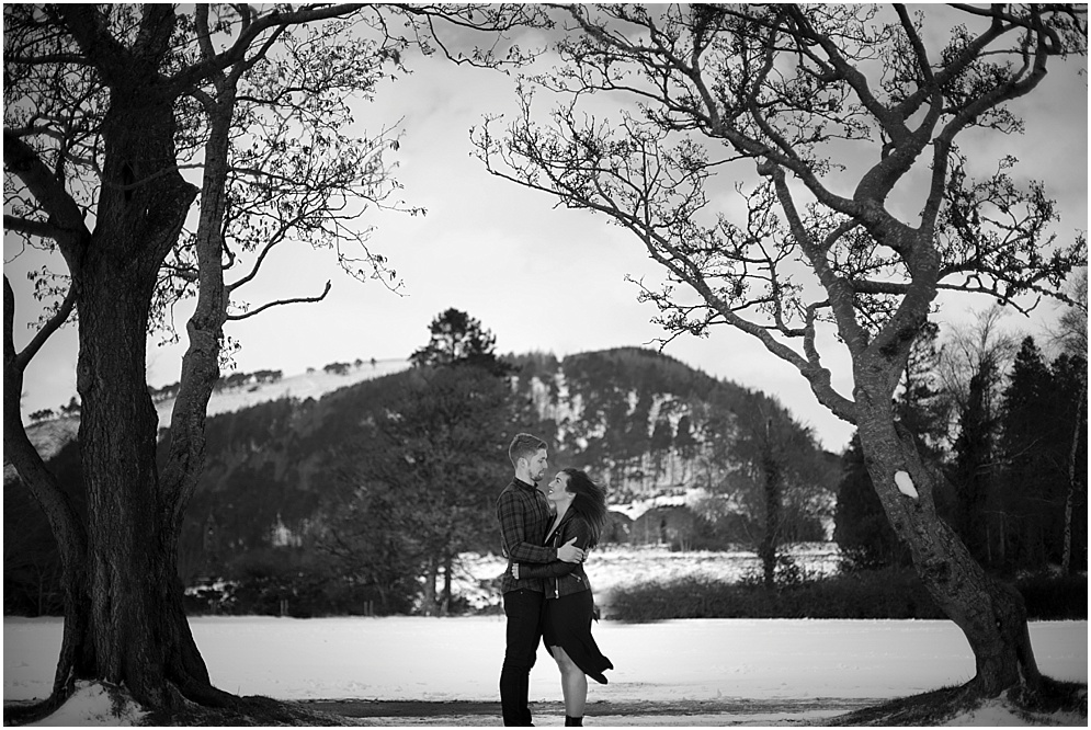 Black and white photograph of a couple pictured in the snow at glendalough in Ireland.