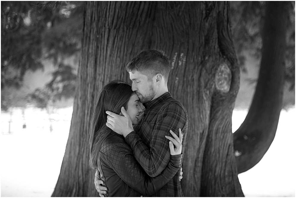 Couple share a kiss by a tree. Lancashire wedding photographer.