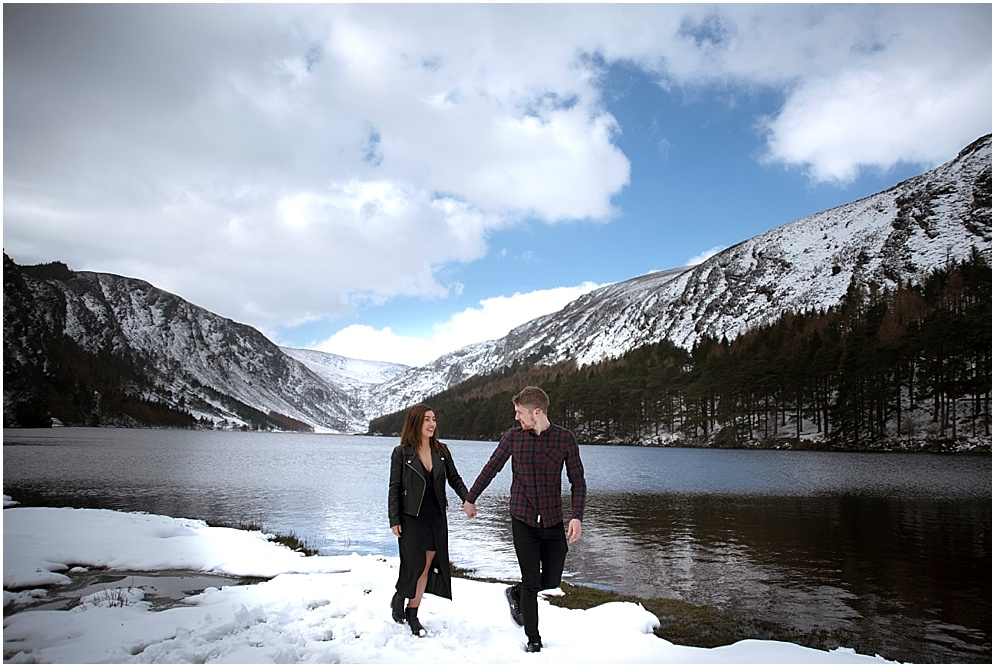 Couple walk along the shore at Glendalough in Ireland.